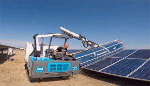صورة تبين عامل يقوم بتنظيف الألواح الشمسية باستخدام ألة تنظيف مركبة على شاحنة
