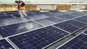 عمال يقومون بعملية التنظيف للألواح الشمسية يدوياً