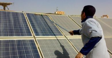 عامل يقوم بتنظيف الألواح الشمسية من الغبار